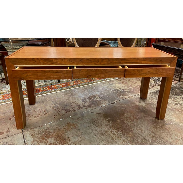Custom made mid-century style console table with 3 drawers. The only decoration is a raised lip, painted gold, that runs...