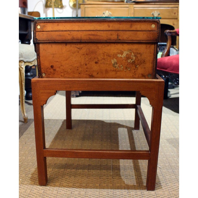 English leather suitcase on stand with glass top.