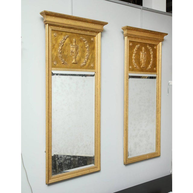 A pair of restrained, yet elegant gilt wood mirrors. The molded frame surrounds the bevelled antiqued glass and a carved...