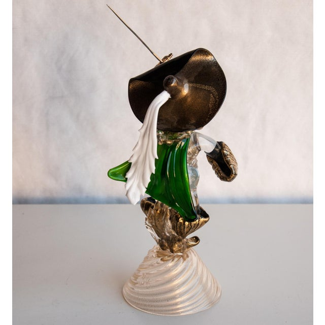 A whimsical and masterfully crafted Cavalier in green, black, white and clear glass with gold inclusions in the style of...