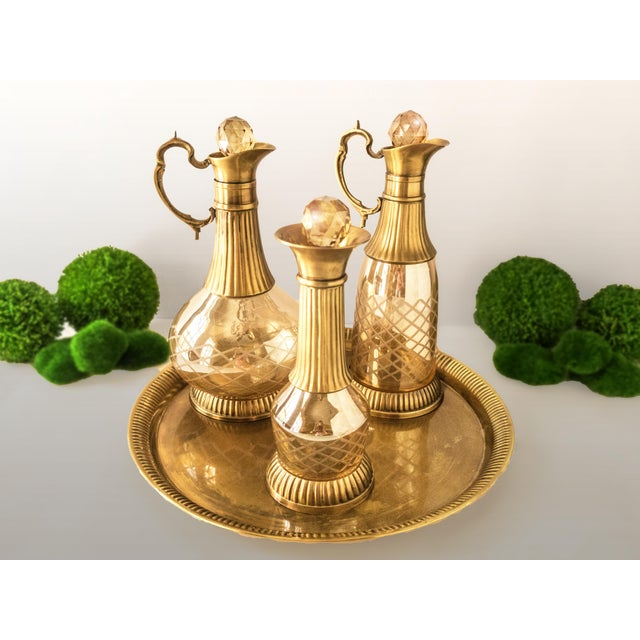 Stunningly gorgeous, brass and amber crystal decanters, set of 3, with brass tray. The decanters are amber, cut crystal,...
