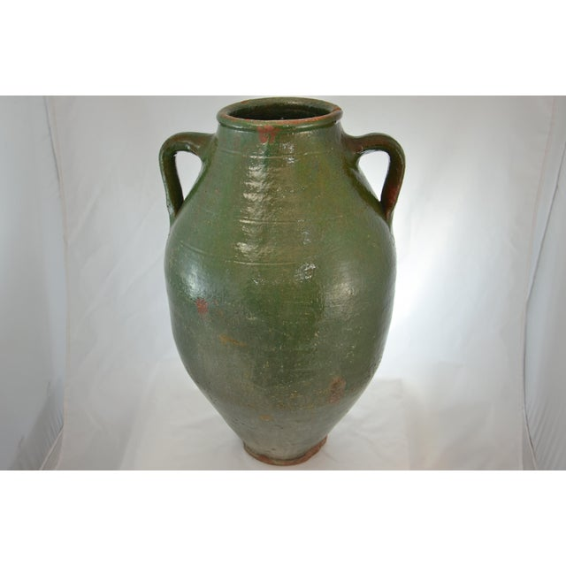 Oversize rustic hand thrown terra cotta two handle jar, glazed inside and out in dark green with black and gray...