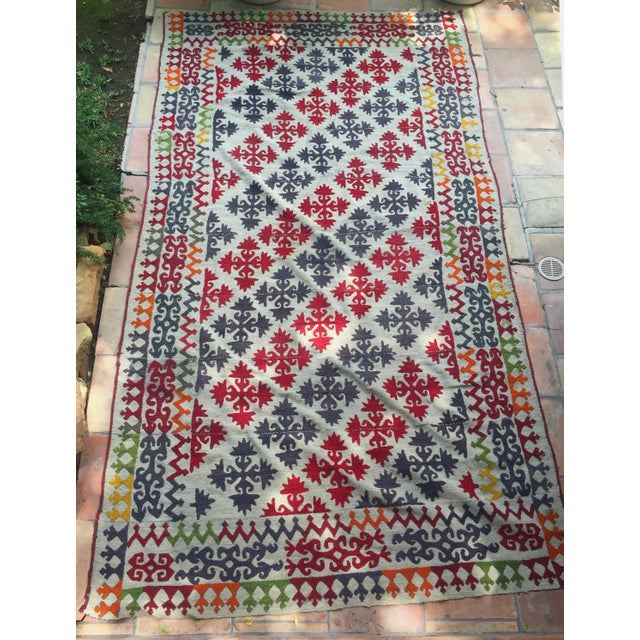 Featuring a colorful pattern of geometric elements, this unique embroidered kilim showcases an array pop 1950s...