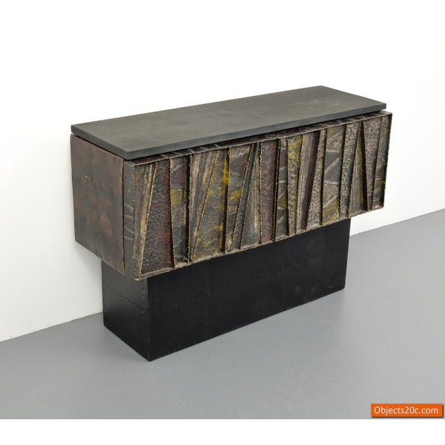 Deep relief wall cabinet with two doors revealing storage by Paul Evans (American, 1931-1987). The cabinet may be wall...