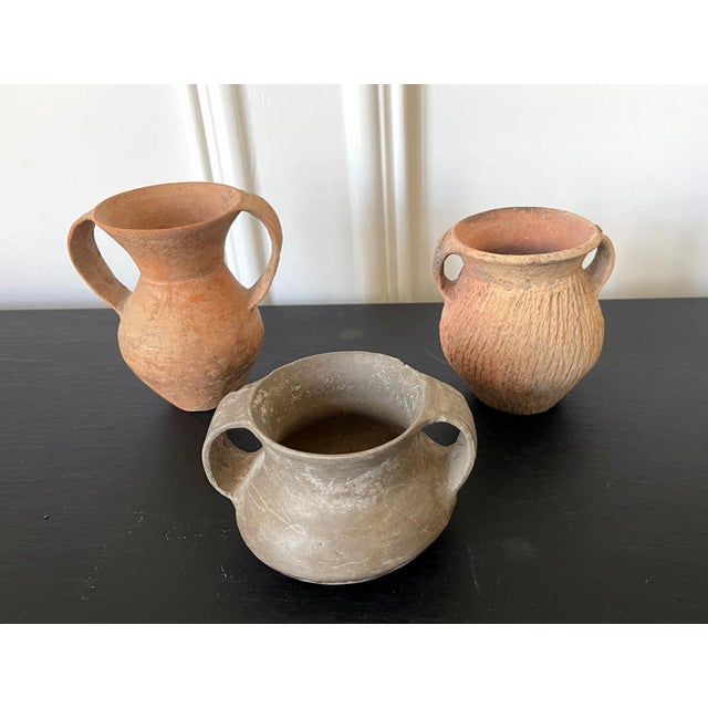 A collection of three small Chinese Neolithic pottery jars consisting a red slender jar with large double ears, a grey and...