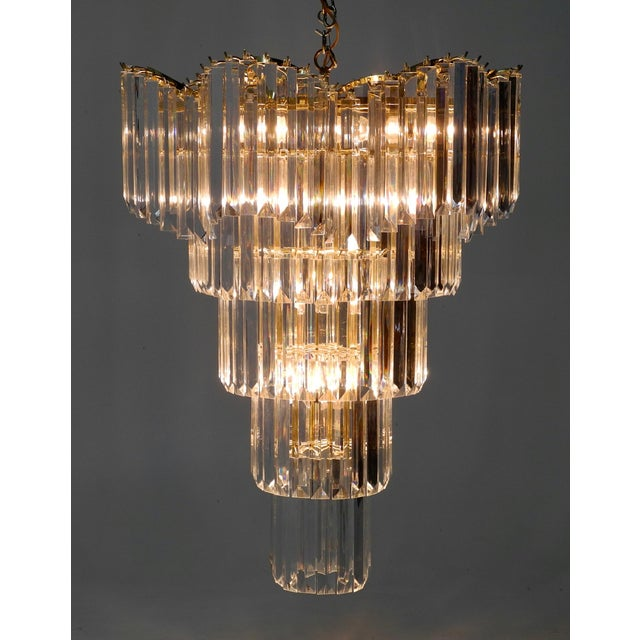 Beautiful Hollywood regency tall chandelier with graduating Lucite prisms. The top tier has an undulating shape all round...