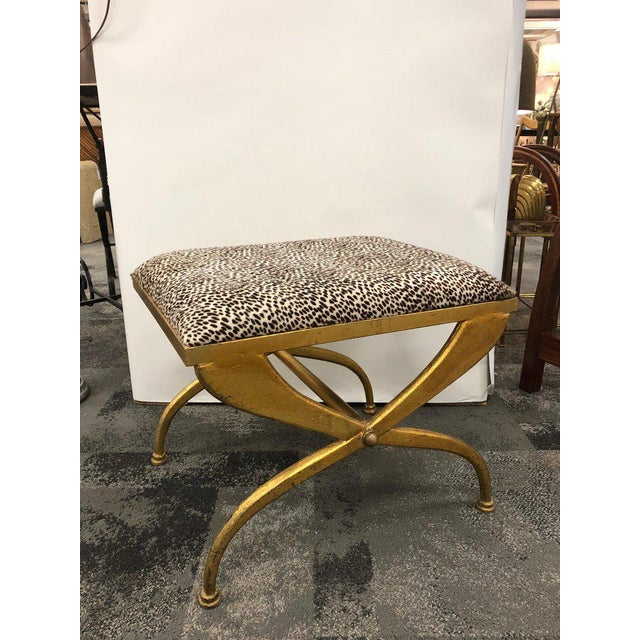 Midcentury French gilt iron bench with cast iron base and cowhide upholstery. Designed by Maison Ramsay.