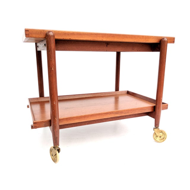 1960s Danish Modern teak rolling bar cart by Poul Hundevad. The bar cart features a sliding top tray and removable lower...