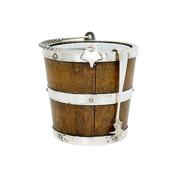English oak ice bucket with silver-plate fittings and removable porcelain liner. Includes claw-tipped ice tongs. Bucket,...