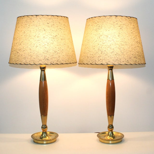 Offered for consideration is an outstanding matched pair of early 1960s teak and brass lamps with fiberglass shades....