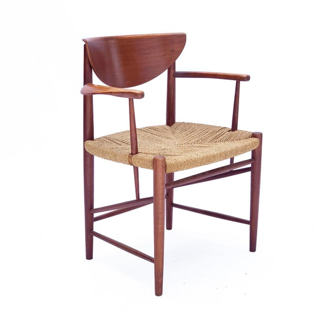 This gorgeous vintage chair is crafted in solid teak with sculptural arms and a half-moon backrest. The seat is woven rope...