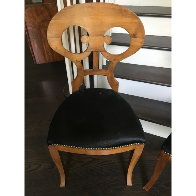 Pair of late 19th Cenutry Biedermeier chairs upholstered in black cowhide with nail head trim.
