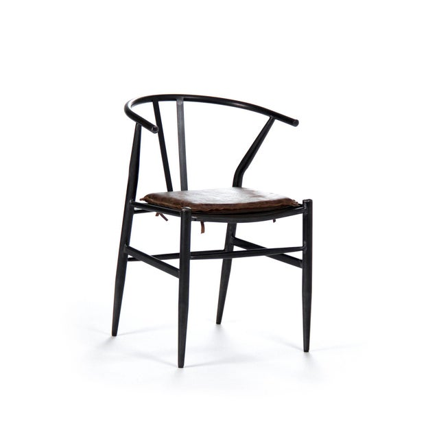 Side chair with a curved back made of metal and top grained leather and a removable seat cushion.