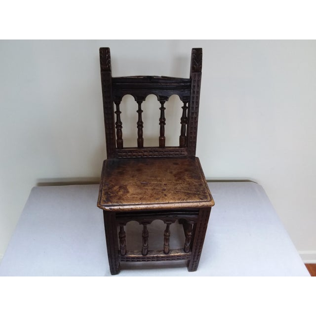 This is a small, primitive rustic chair with a beautiful patina. It features hand turned spindles and notched carved...