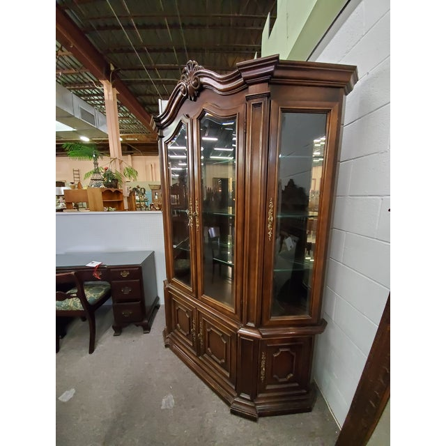 Vintage china cabinet with four beveled glass doors nad three glass shelves inside, above four wood doors with a shelf...
