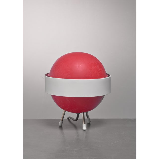 A small, mid-century Stilux 'Saturn' table lamp. The lamp is made of a red aluminum globe with white aluminum band around...