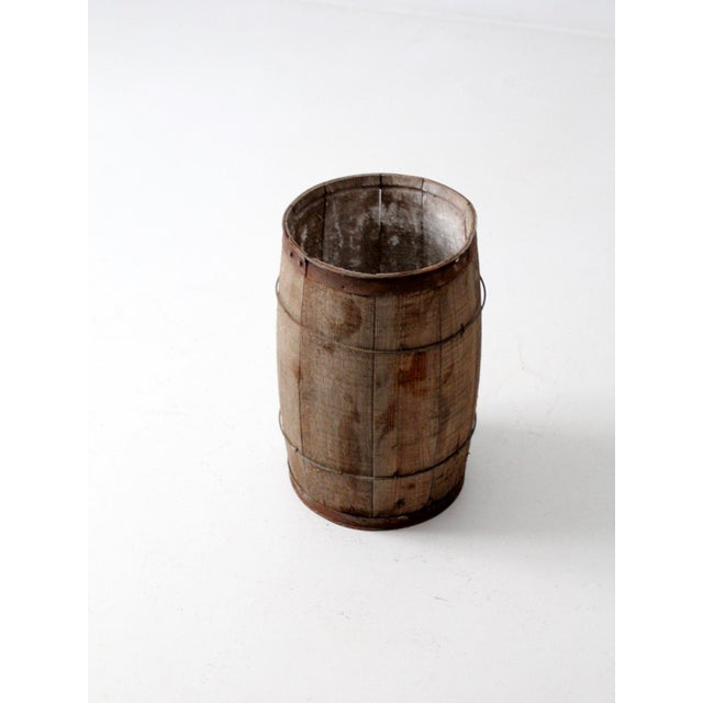 This is an antique primitive barrel. The rustic wooden keg features wood slats and metal banding. In good condition with...