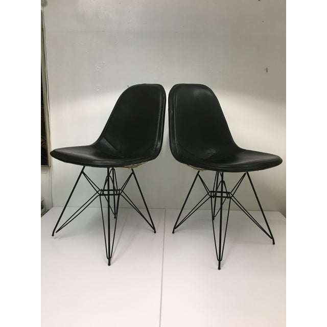 Authentic from the mid-century era, this pair of classic Eames chairs feature powder-coated white wire seats on iconic...