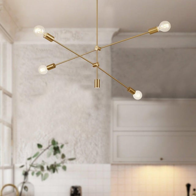 Inspired by industrial sculptures of the 1930s the Elena chandelier offers a visually stunning modern silhouette. The gold...