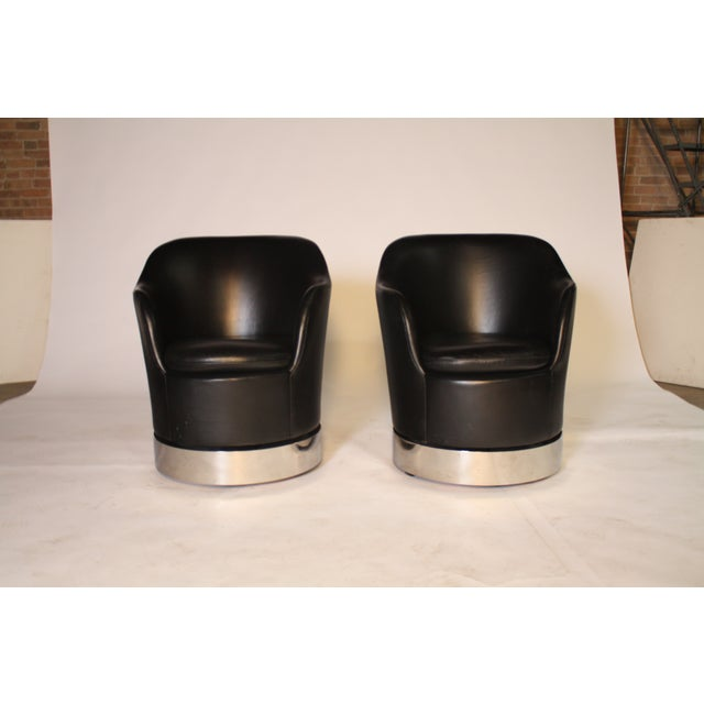 Original pair of vintage 1970s black leather swivel chairs by Phillip Enfield, N.Y. on polished steel base and concealed...