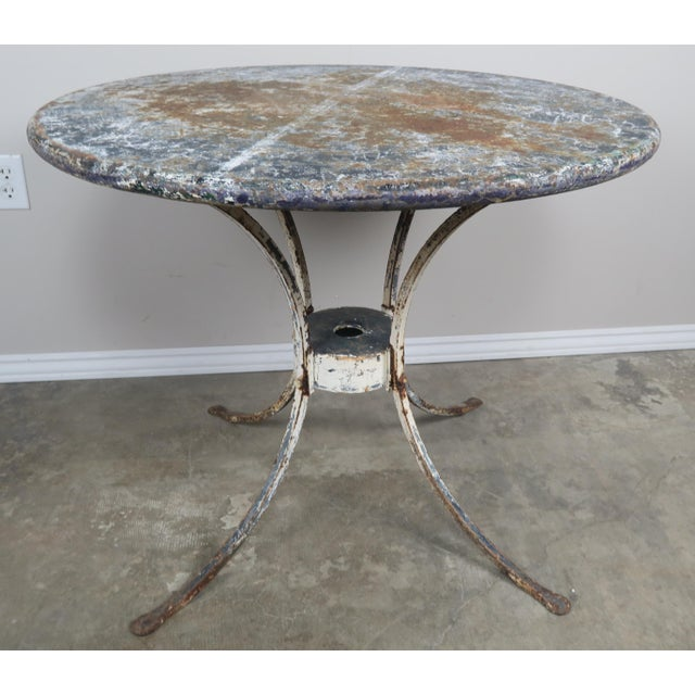 Painted metal garden table with worn distressed finish.