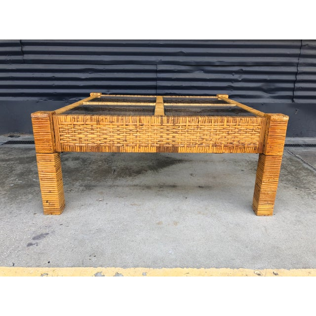 Vintage wrapped rattan coffee table in the style of Billy Baldwin. Features woven sides with wrapped legs and a four glass...