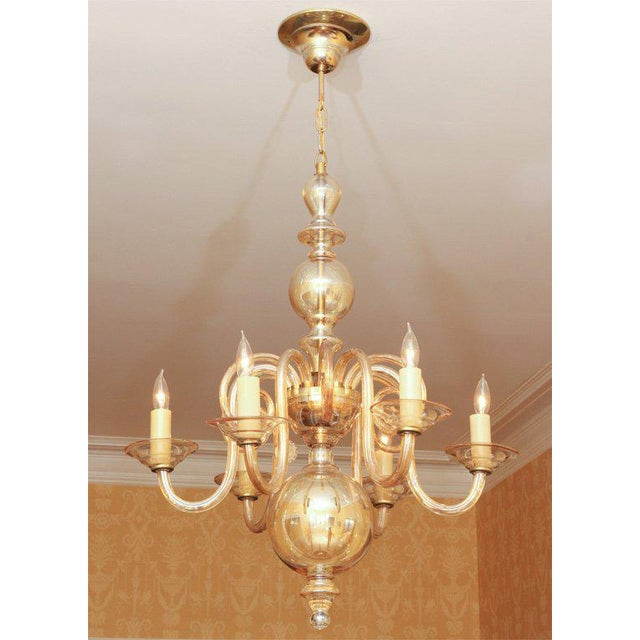 A lovely amber glass six-arm chandelier with a centre globe, six lights above round glass bobeches, and an additional six...