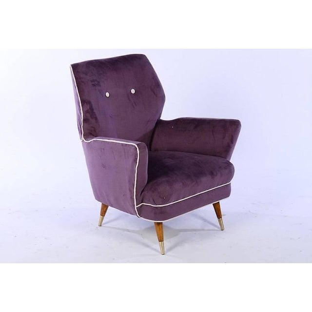 A pair of Italian Mid-Century Modern upholstered club chairs raised on turned and tapered legs with brass caps, circa...