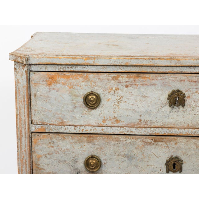 A blue painted Gustavian chest of drawers ca. 1790 features classic elements of the period. Historic blue paint shows some...