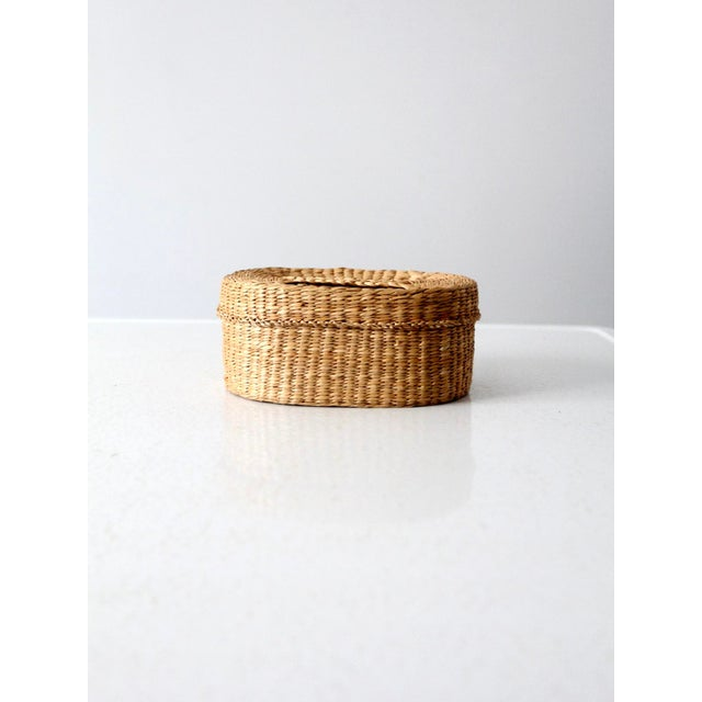 Organize your space with this vintage sweetgrass basket. The small woven basket features a lid with slender handle.