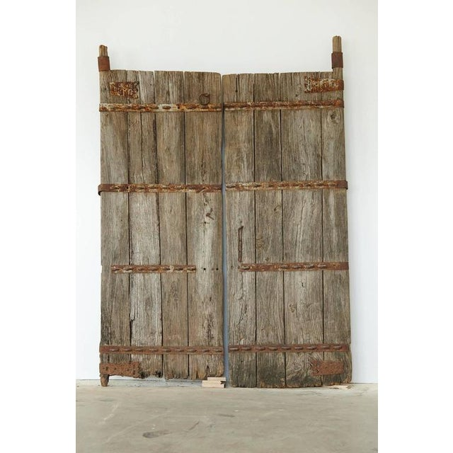 Pair of unrestored Chinese gate doors in heavy, reinforced solid oak with hand-forged metal applications. The depth of the...