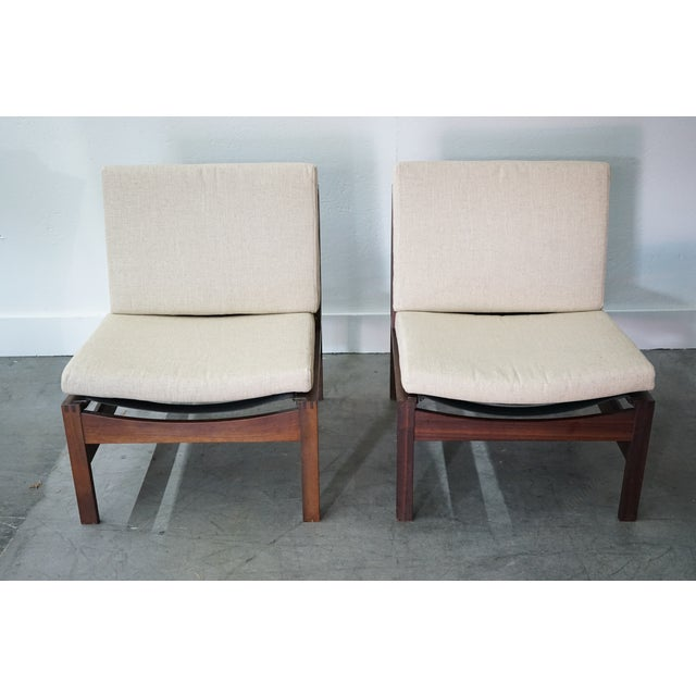 These are a pair of Italian mid-century teak lounge chairs with removable white upholstery back and seat cushions, circa...