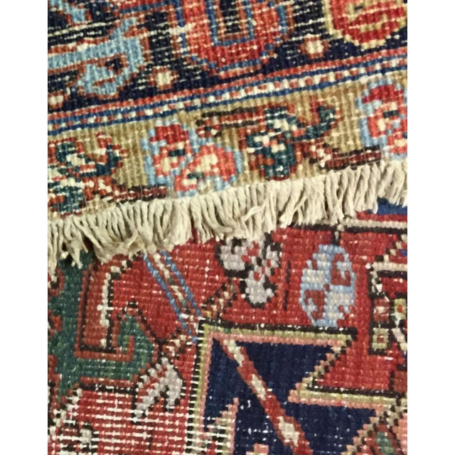 Handwoven wool Persian heriz rug with a traditional design, circa 1930. Lightly distressed, low pile. Color: red/blue/ivory