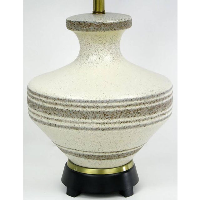 Hand thrown pottery table lamp attributed to Lightolier, with oriental urn shaped ceramic body glazed in speckled cream...