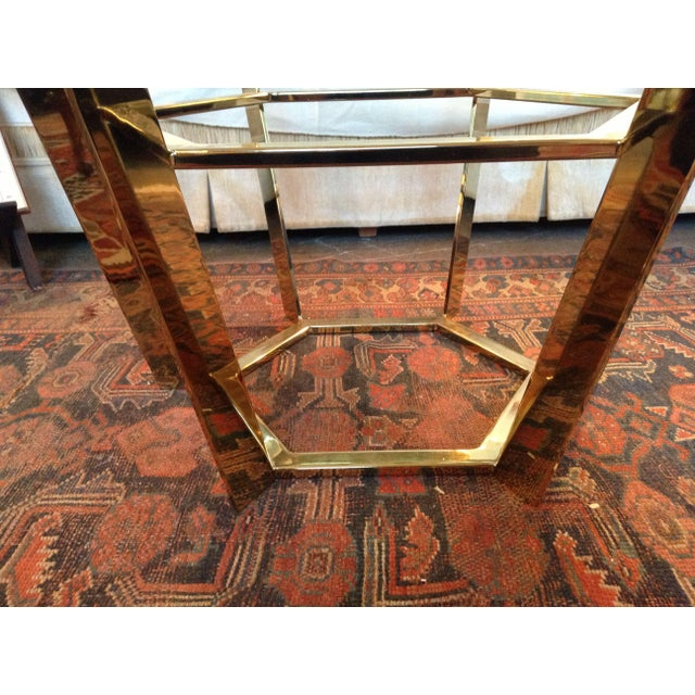 A gorgeous 70s modern brass and glass coffee table. The table features a brass flat bar sunburst style frame. The frame...