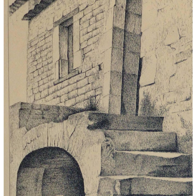 Vintage French lithograph of a rustic stone building and stairway with a figure in the shade of an alcove by artist Andre...