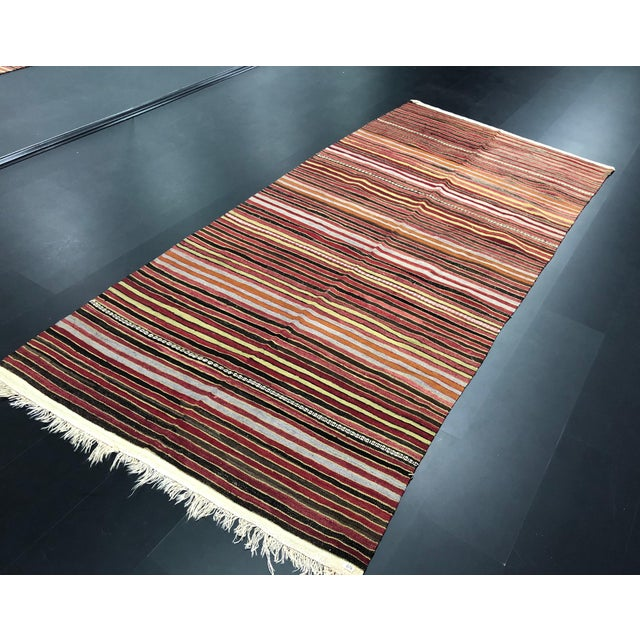 This is a vintage kilim rug. The piece was handmade in the 1960s.