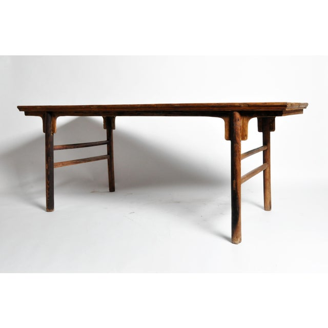 This Chinese painting table is from the early Qing Dynasty and is made from elm wood. It features a beautiful aged patina.