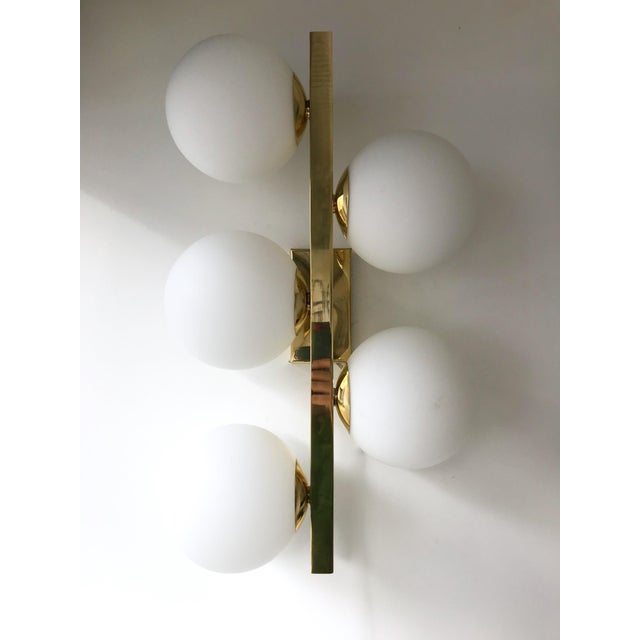 Contemporary gilt brass wall lights sconces, blown Murano opaline tick glass ball. Few exclusive artisanal production. In...