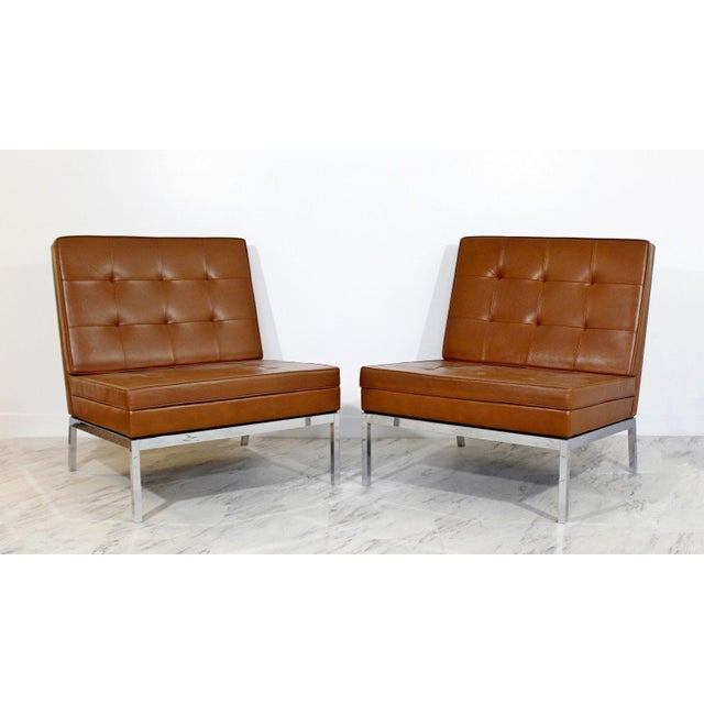 For your consideration is a phenomenal pair of chrome and brown leather slipper chairs, model #65, by Florence Knoll,...