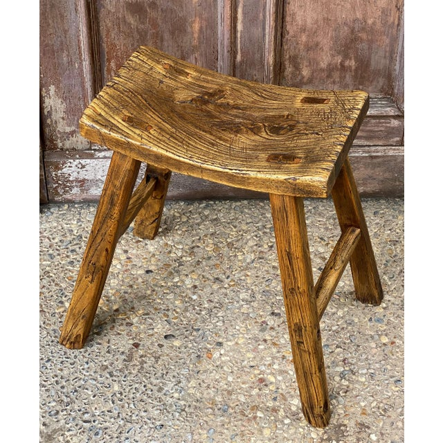 A fine English saddle seat or rustic farm stool of elm, featuring a shaped rectangular seat over four legs.