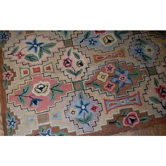 Antique American hooked wool rug, Circa 1900. Beautiful allover mixed geometric and floral design on beige ground. In...