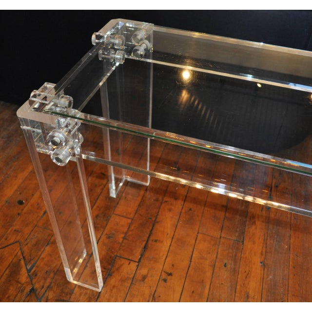Sculptural Mid-Century Modern Lucite console or sofa table with center rod stretcher and bolted trim details. Thick Lucite...