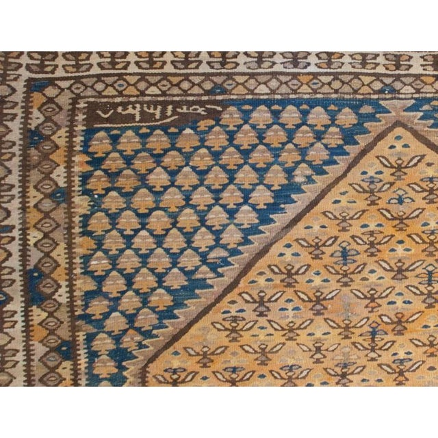 A wonderful early 20th century Persian Senneh kilim runner with a beautiful indigo diamond medallion with gold and brown...