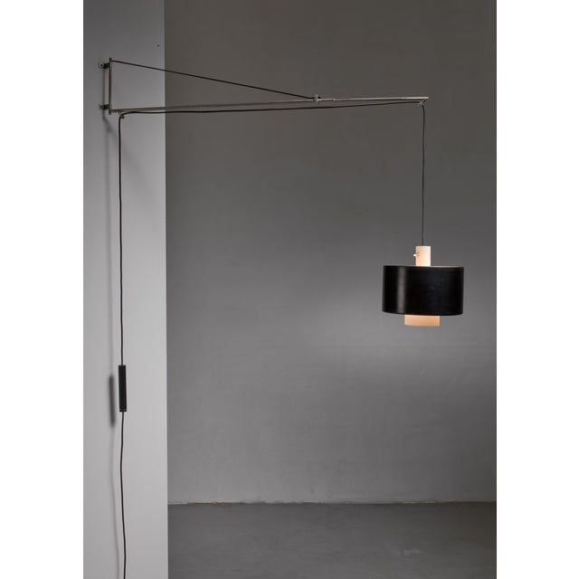 A metal model 2061 wall lamp designed in 1954 by Gaetano Sciolari for Stilnovo, Italy. The swiveling lamp has a nickel...