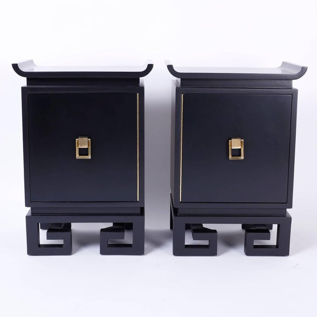 Chic pair of black lacquered bedside chests or nightstands with the distinctive James Mont influence. Featuring a Ming...