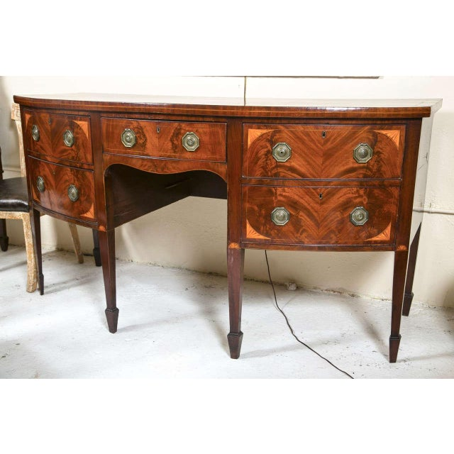 English Georgian style mahogany sideboard. Features bow-shaped top with satinwood and ebony inlaid border. Single central...