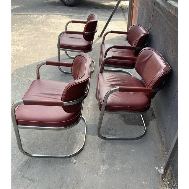 Distinctive red vinyl and chrome, four dining chair set. Patina and cantilever design make this collection a mid-century...