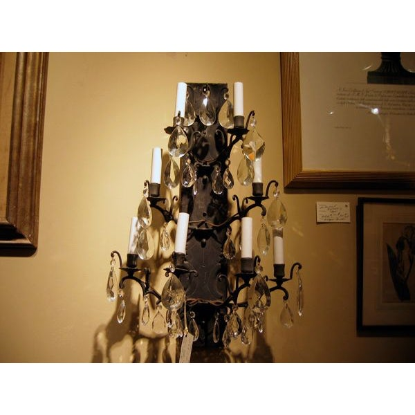 """Fine pair of designer quality antique iron and crystal wall sconces. Each measures approximately 15"""" wide x 8"""" deep x 25""""..."""