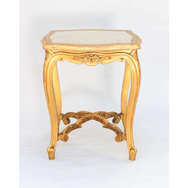 Carved giltwood accent table, having a distressed mirrored top inset in frame, apron with floral details, raised on...